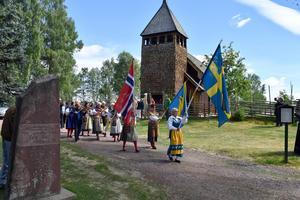 Maria Bäckman leder tåget från gammelkyrkan till Kyrkbacksgården med den svenska fanan, som sedan följs av den norska.