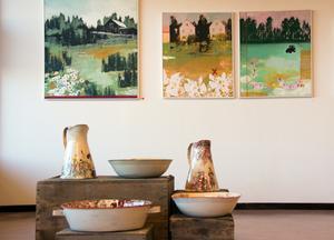 Anna Wrigstad Östbergs keramikföremål är gammaldags både i form, blomsterutsmyckning och de äldre bilder de bär på. Ylva Bomarks väggkonst stämmer in i samma tal om landsbygd, trygghet och tidlöshet.