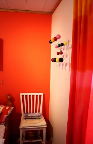Väggfärgen matchar med Marimekko-gardinerna.