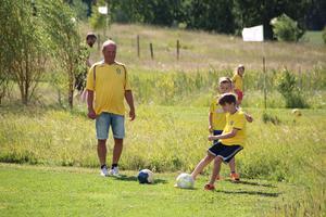 Pensionär Esbjörn Erlandsson driver Vållens Fotbollsgolf så gott som dagligen. Här spelar han med Hugo Eriksson, 8 år (bakom),  och Roanin Vrtiska, 10 år (på bollen). I bakgrunden syns pappa Scott Vrtiska spela tillsammans med dottern Adrienne, 6, på en annan bana.