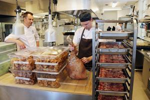 Köksmästare Michael Westelius med Daniel Coyet som handskas med köttet från en Linderödgris.