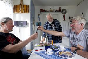 Paul Fogelman, Ulf Westin och Roffe Persson tittar på bilder från resan över en kopp kaffe.