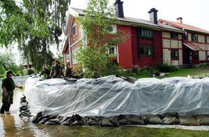 Sommaren 2000 byggde man upp en vall av sandsäckar kring huset för att skydda det mot vatten.Foto: Kjell Jansson