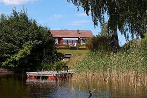 Stuga intill sjön med egen båtbrygga, inglasat uterum och en rymlig trädgård. Foto: Carin Heed