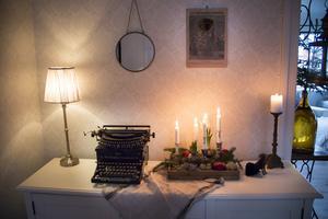 På skänken i matsalen lyser adventsljusen. Den antika skrivmaskinen av märket Remington är en av Karins favoritprylar i hemmet.