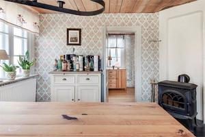 Kamin och tidstypiska tapeter i vardagsrummet. Foto: Fastighetsbyrån Köping