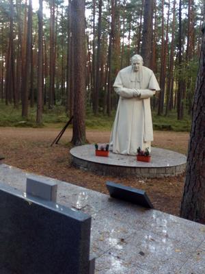 Påven Johannes Paulius,  själv polack, har besökt massgravarna och står som staty. Foto: Eva Hansson.