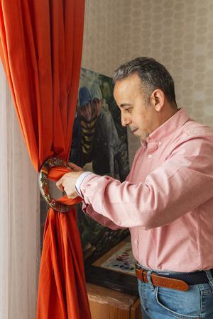 Fokuserat sätter Osama Zamzam i gardinerna i det målade träfästet som familjen fick med sig i flytten från Saudiarabien.