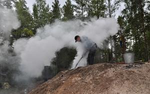 Mitt i röken står en kunnig Ydrekolare redo att göra den snabba insats som krävs för att veden i milan inte ska brinna upp.