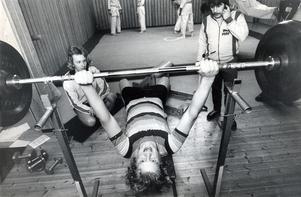 Bjurhovda fritidsgård 12 januari 1974. Man kan ägna sig åt styrketräning. Jonny Spjut leder övningarna. Anders Klum tittar på, medan Öivind Aanäs kämpar med skivstången.