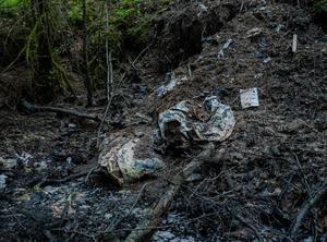 På en plats någonstans längs med Nossan hittade Thomas en mindre soptipp bristfälligt nedgrävd, där skräpet med tiden hade flutit ut i den intilliggande ån.