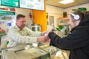 Här serverar Pelle Eriksson en av de första kunderna under måndagen. Kunden Elias har precis beställt en rykande panini.