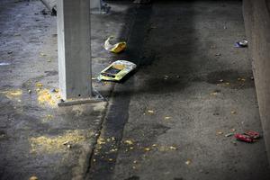 Ölburkar, juiceförpackningar och cigarettpaket skräpar i parkeringshuset trots städning dagen innan.
