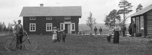 Den förste lanthandlaren i Börtnan Anders Åström med sin cykel utanför butiken, 1898. Till höger syns hustrun Agnes med sonen Per. Framför affären står de övriga barnen Julia, Märta och Jon. I affären såldes det bland annat snus, salt, tobak, såpa, socker och kaffe. Fotograf okänd