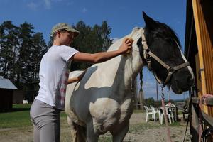Lägerdeltagare Julia svalkar av hästen Willy med vatten efter dagens ridpass.