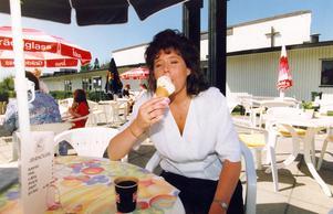 Sommarkafé på Bäckby i maj 1992. Carina Karlsson, heltidsanställd vid Café Jacobs brunn, svalkar sig med en glass i sommarhettan. Vid Bäckbys nya uteservering samlas både gammal som ung.