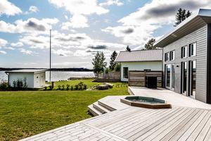En pool nedsänkt i trädäcket och ett stenkast från strandkanten. En nyproducerad villa i Ulvviksstrand är till salu för 3 250 000 kronor. Foto: Pär Olert.