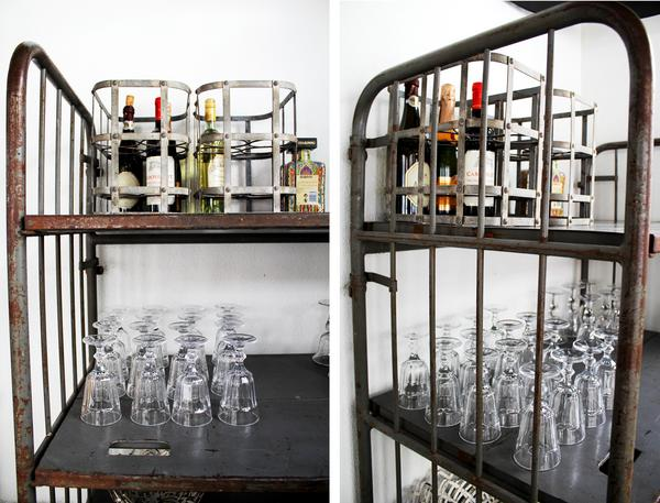 En vagn med patina bär glas och flaskor i uterummet.
