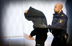 Den misstänkte 30-åringen lämnar rättssalen tillsammans med en polis efter att häktningsförhandlingen avslutats.