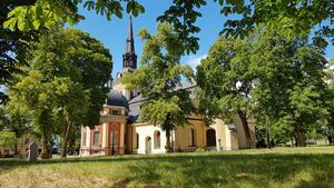 S:ta Ragnhilds kyrka ramas under sommartid in i grönska.