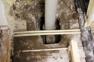 Röret kommer uppifrån taket och ska leda regnvatten till dagvattenbrunnen. På grund av att någon kört ner långa störar i röret så har vatten läckt ut i betongen under trägolvet. Händelsen är polisanmäld.