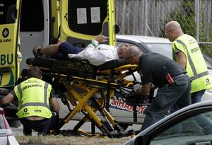 En man förs bort av ambulanspersonal efter dådet i Christchurch i Nya Zeeland. Olika terrorgrupper som hatar varandra, står egentligen varandra nära, skriver Lars Ströman.
