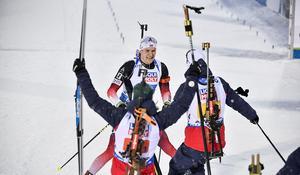 Norges sista åkare har precis skurit mållinjen och säkrat VM-guldet i mixstafett till Norge. Vetle Sjaastad Christiansen tas emot av jublande lagkompisar. Foto: TT/Anders Wiklund