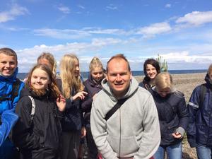 Jonas Ahlsson i grå jacka omgiven av sina konfirmander på lägret i Bunge på Gotland.