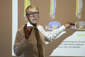 Överläkaren Thomas Björk-Eriksson som är medicinskt ansvarig på kliniken visar med bilder hur mycket den onödiga strålningen kan minskas med protonbehandling.