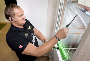 Vågrätt. Ivan Pleinadius tvättar fönstret med en påläggare med mikrofibrer och drar sedan vågrätt med skrapan. För att slippa spill på golvet håller han kvar påläggaren längst ner på fönstret.