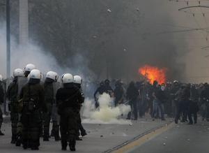 Protesters throw stones to riot police during clashes in central Athens on Sunday, Dec. 7, 2008. Riots broke out Sunday in the Greek capital as demonstrators protested the fatal police shooting of a teenager in Athens the previous night. Youths hurled firebombs, rocks and other objects at riot police, who responded with tear gas. The circumstances surrounding the shooting of a 16-year-old boy by a police special guard in the downtown Athens district of Exarchia are still unclear. But the death triggered extensive riots in cities around the country overnight, with youths burning shops, setting up flaming barricades across streets and torching cars. (AP Photo/Thanassis Stavrakis)