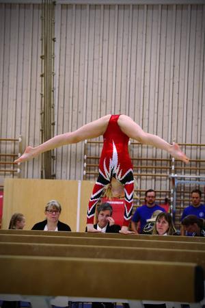 En gymnast visar upp sina kunskaper på bommen under insyn av domarna.