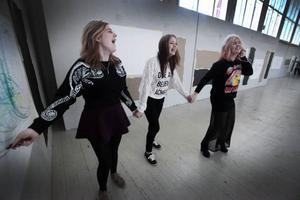 Johanna Berglind, Josefine Arwhem och Cassandra Hemmingsson arbetar tillsammans. Cassandra Hemmingsson lyssnar på musik i hörlurar och dansar, Josefine Arwhem följer hennes rörelser som via Johanna Berglind krita hamnar på en vit duk.