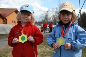 Elida Olsson och Signe Persson, båda från Furans förskola, visar upp sina blommedaljer de fick vid målgången. De tycker det hade gått bra att springa.