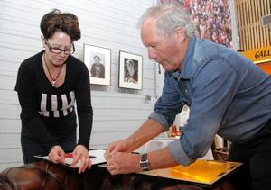 Margaretha Hammarström hjälper Villy Holmberg att hänga upp fotografierna inför utställningen.