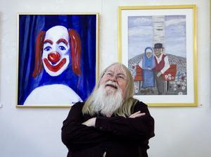 Stefan Daagarsson vid två av sina egna tavlor, som hänger kvar efter sommarens utställning.