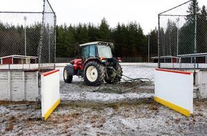 """I stället för att spola isen får Urban Persson från Hara harva bort sten från hockeyrinken. """"I fjol den här tiden hade vi jättefin is"""", säger han.Foto: Jan Andersson"""
