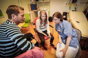 Daniel Ivarsson, Stina Ivarsson och läkare Anna-Lena Fureman tittar på den dosa som scannar av Stinas blodsockervärden.