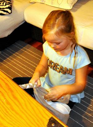 Nora föredrar att sätta fast fleeceremsorna i kistan i vardagsrummet när hon ska göra sina hundleksaker.