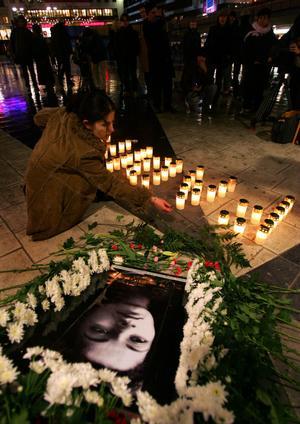 """Minnesmanifestation 2005 i Stockholm för Fadime Sahindal. Sara Mohammad ordförande i riksföreningen """"Glöm Aldrig Pela och Fadime"""" ordnar till blommarna vid Fadimes porträtt."""