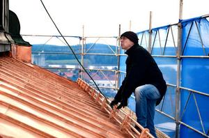 Konservatorn Johan Dahl har förgyllt korset och urtavlorna med cirka 3 000 ark bladguld.