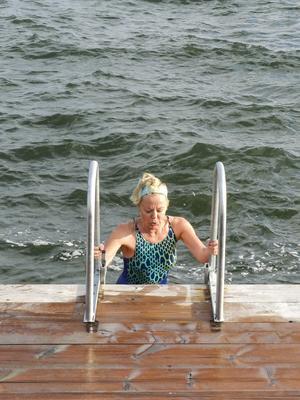 Att ta ett dopp i det iskalla vattnet mellan bastubadandet sägs vara bra för blodcirkulationen. Guiden Heidi Tetri visar hur det går till.