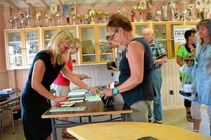 På löpande band. Annelie Bernström säljer brickor till Inger Wilhelmsson.