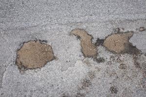 Vintern har tagit asfalten med sig och lämnat grusfyllda gropar efter sig.