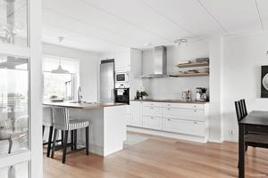 Köket och allrummet i Bydalen går i vitt med inslag av svart och naturnära toner.