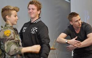 Johannes Hansen visar eleverna Leonard Lundback och Felix Sjöblom hur de ska våga kramas på scenen.  Foto: Christer Klockarås