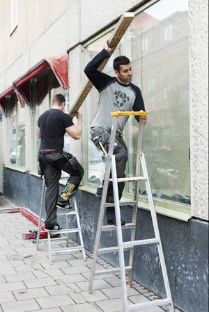 Jimmy Olsson och Daniel Magnusson arbetar med att sätta upp nya markiser åt Restaurang T&K i Östersund som öppnar på fredag.
