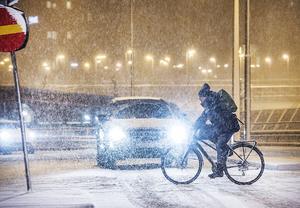 En cyklist kämpar sig fram i kraftigt snöfall