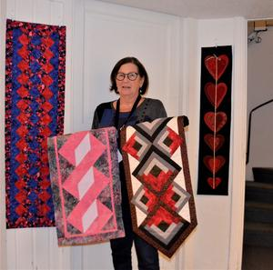 Kerstin Heldeby ställer bland annat ut  dessa bomullsdukar, den till höger som hon håller i  har stockhusrutan som mönster. Till vänster på väggen en duk med fruktmotiv.