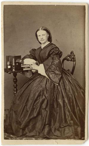 Fotografen B C F Sandberg (verksam i Hudiksvall 1863–1867) har tagit bilden på sin syster Mathilda som sitter vid en typisk kamera från 1860-talet. Bild från Hälsinglands museum.